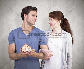 Composite image of couple holding a model house