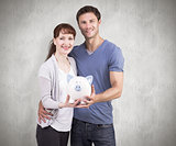 Composite image of couple holding a white piggy bank