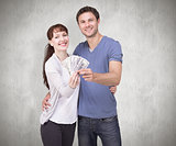 Composite image of couple holding fan of cash
