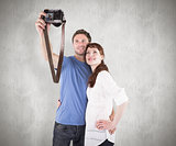 Composite image of couple using camera for picture