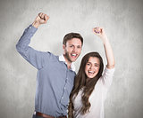 Composite image of happy young couple cheering