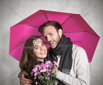 Composite image of cheerful young couple with flowers and umbrella