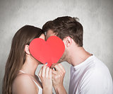 Composite image of side view of romantic couple holding heart