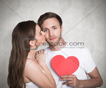 Composite image of woman kissing man as he holds heart