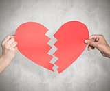 Composite image of two hands holding broken heart