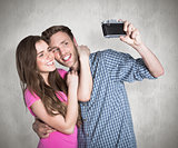 Composite image of couple taking selfie with digital camera