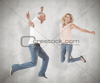 Composite image of excited couple cheering and jumping