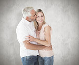 Composite image of affectionate man kissing his wife on the cheek