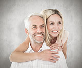Composite image of happy man giving his partner a piggy back