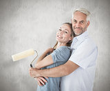 Composite image of happy couple hugging and holding paint roller