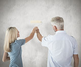 Composite image of happy couple painting wall with roller