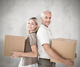 Composite image of happy couple holding moving boxes