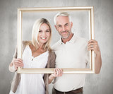 Composite image of happy couple holding a picture frame