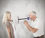 Composite image of angry man shouting at girlfriend through megaphone