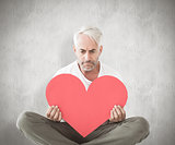 Composite image of upset man sitting holding heart shape