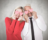 Composite image of silly couple holding hearts over their eyes