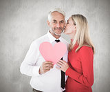 Composite image of handsome man holding paper heart getting a kiss from wife