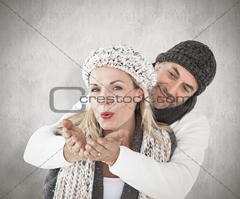 Composite image of smiling couple in winter fashion posing