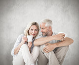 Composite image of happy couple sitting holding mugs