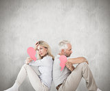 Composite image of unhappy couple sitting holding two halves of broken heart