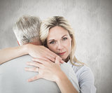 Composite image of unhappy blonde hugging her husband