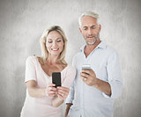 Composite image of happy couple texting on their smartphones