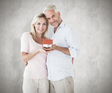Composite image of happy couple holding miniature model house