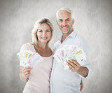 Composite image of happy couple flashing their cash