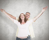 Composite image of casual couple smiling with arms raised