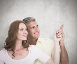Composite image of casual couple smiling and pointing