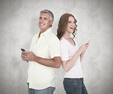 Composite image of casual couple sending text messages