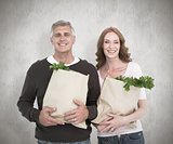 Composite image of casual couple holding grocery bags