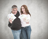 Composite image of casual couple showing their cash