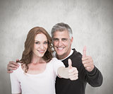 Composite image of casual couple showing thumbs up