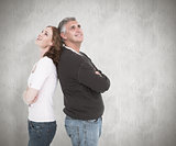 Composite image of casual couple smiling and looking up