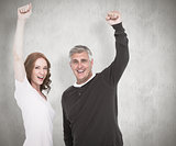 Composite image of casual couple cheering at camera