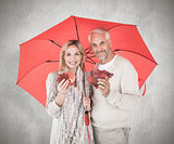 Composite image of smiling couple showing autumn leaves under umbrella