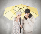 Composite image of couple in winter fashion sneezing under umbrella