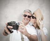 Composite image of vacationing couple taking photo
