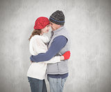 Composite image of happy couple in warm clothing hugging