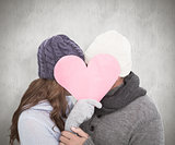 Composite image of couple in warm clothing holding heart