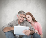 Composite image of casual couple sitting using tablet
