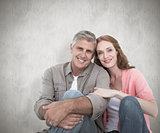 Composite image of casual couple sitting and smiling