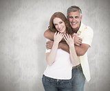 Composite image of casual couple smiling and hugging
