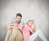 Composite image of attractive young couple sitting holding two halves of broken heart