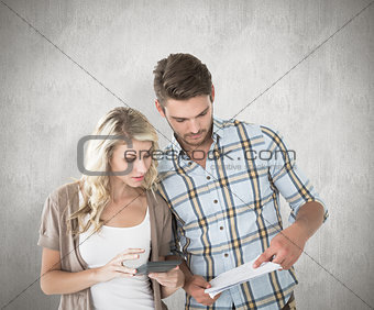 Composite image of attractive couple working out their finances