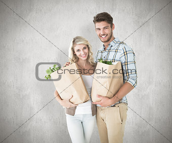 Composite image of attractive couple holding their grocery bags