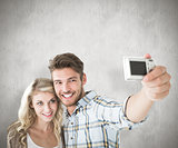 Composite image of attractive couple taking a selfie together