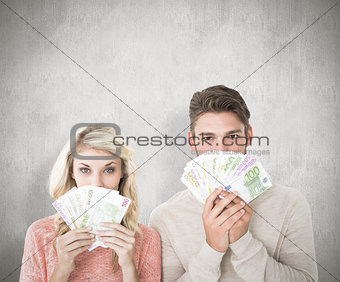 Composite image of attractive couple flashing their cash