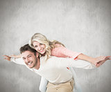 Composite image of handsome man giving piggy back to his girlfriend